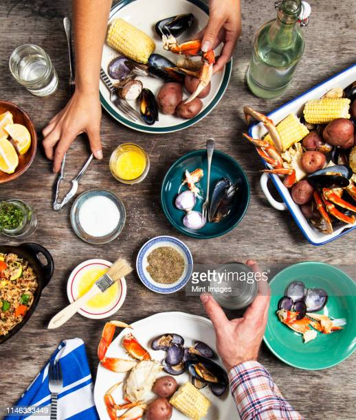 high angle view of hands at seafood dinner - fish love stock pictures, royalty-free photos & images