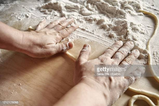 high angle view of hands cutting board on table preparation of fresh tuscan pasta pici - italian food stock pictures, royalty-free photos & images