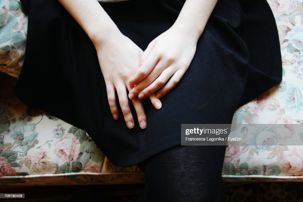 High Angle View Of Hands Of A Young Woman On Lap : Stock Photo