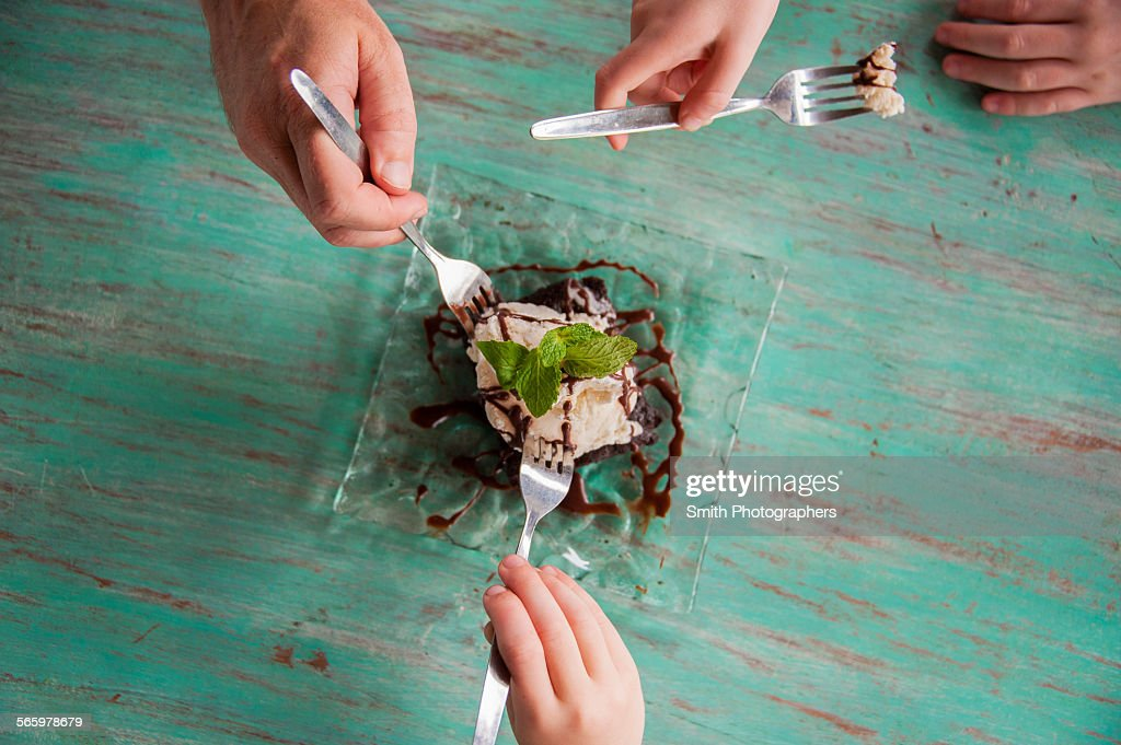 High angle view of hands reaching for food on plate : Stock Photo