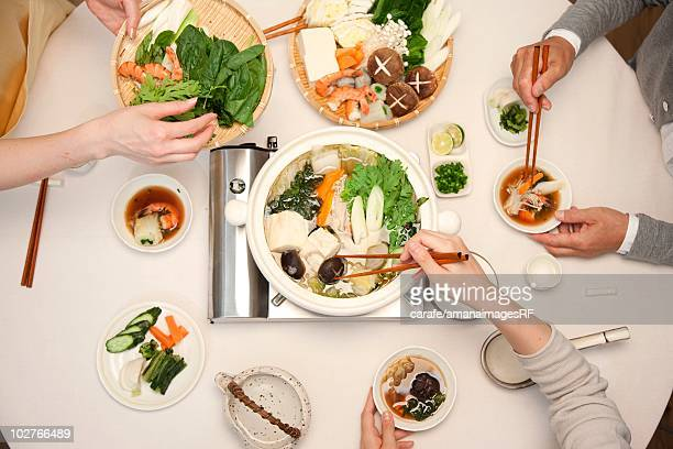 High angle view of hands serving themselves dinner at a table