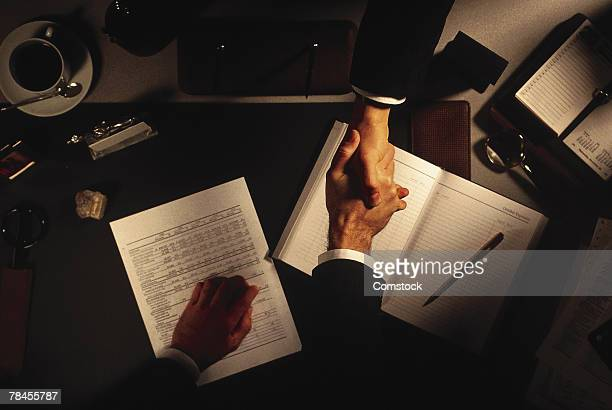 High angle view of hands shaking across desk