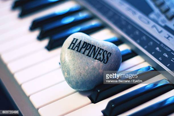 High Angle View Of Happiness Text On Heart Shape Rock Over Piano Key