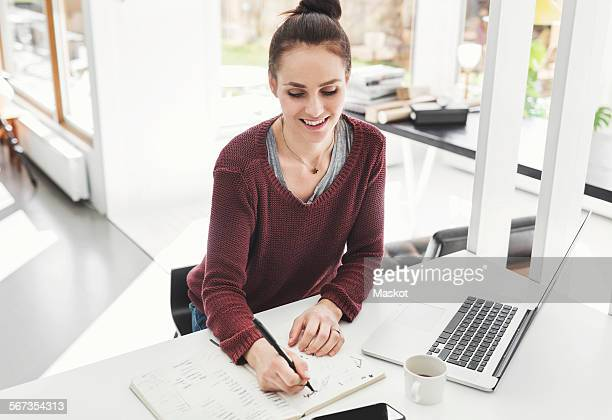 High angle view of happy architect writing in book at desk in home office