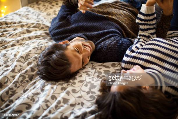 High angle view of happy couple lying on alcove window seat at home