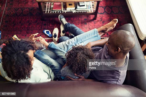 High angle view of happy family sitting on sofa