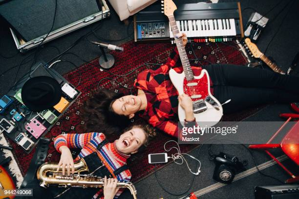 high angle view of happy female musicians playing instruments while lying on carpet - entertainment occupation stock pictures, royalty-free photos & images