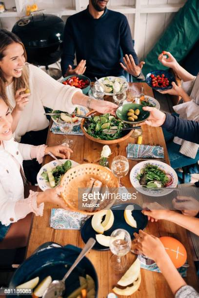 High angle view of happy friends enjoying food in cottage