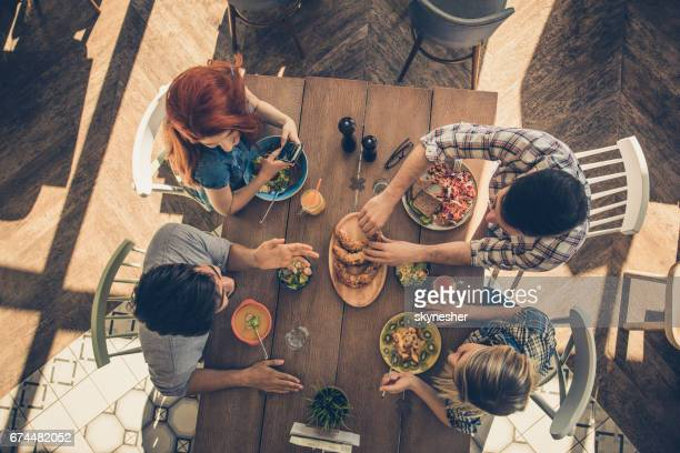 High angle view of happy friends sitting on a lunch in a restaurant and talking.