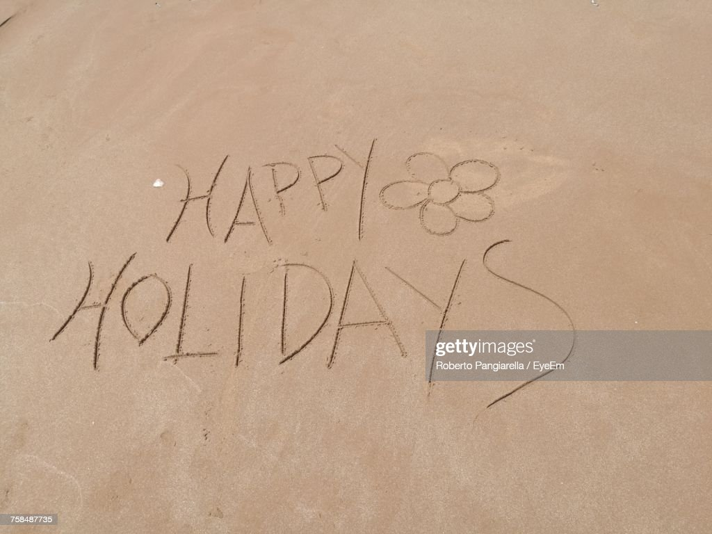 High Angle View Of Happy Holidays Text On Sand At Beach : Stock Photo