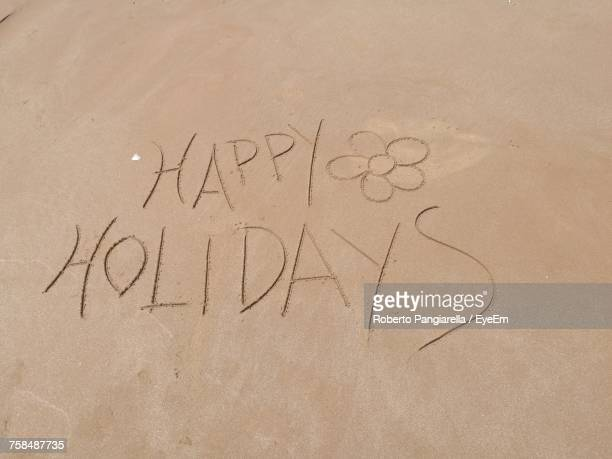 high angle view of happy holidays text on sand at beach - happy holidays stock photos and pictures