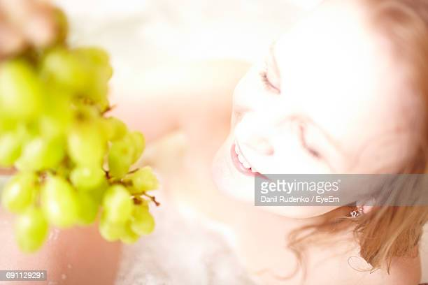 High Angle View Of Happy Woman Bathing With Fresh Grapes