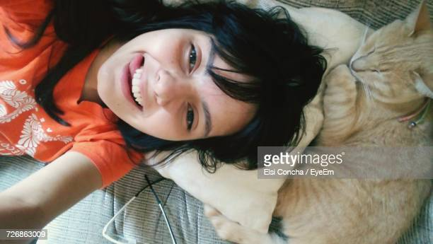 High Angle View Of Happy Woman Lying On Bed With Cat