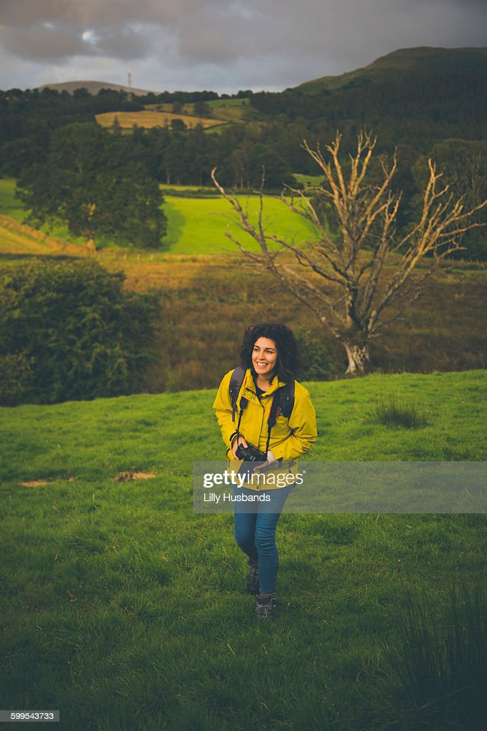 High angle view of happy woman with camera on grassy hill : Stock Photo