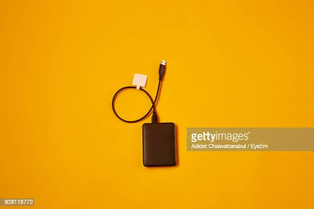 High Angle View Of Hard Disk Drive Over Yellow Background