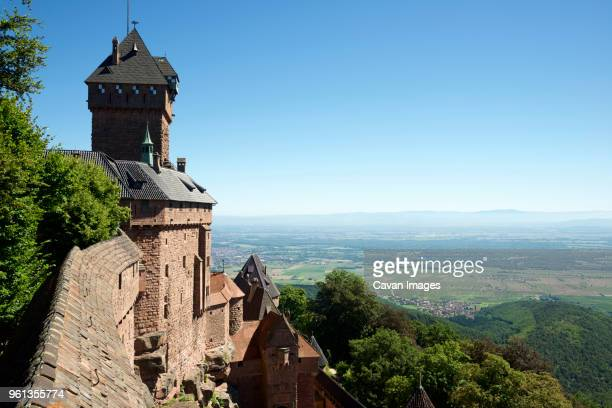 High angle view of Haut-Koenigsbourg Castle by field against clear blue sky