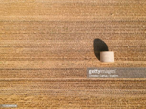 high angle view of hay bale on field - stroh stock-fotos und bilder