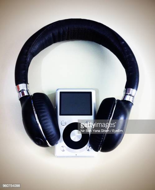 high angle view of headphones with mp3 player on white background - mp3 player stock pictures, royalty-free photos & images