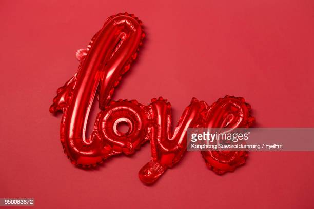 High Angle View Of Heart Shape Balloon Against Red Background
