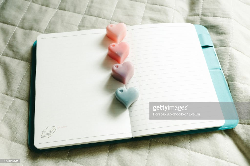 High Angle View Of Heart Shape Candies On Book Over Table : Stock Photo