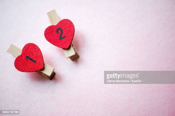 High Angle View Of Heart Shape Clothespins On Pink Background