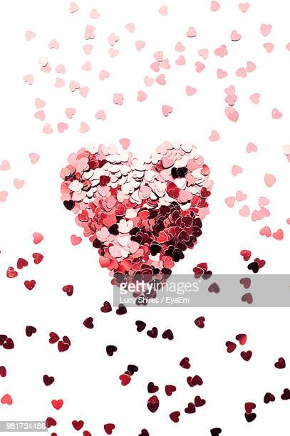 high angle view of heart shape decorations over white background - lucy shires stock pictures, royalty-free photos & images