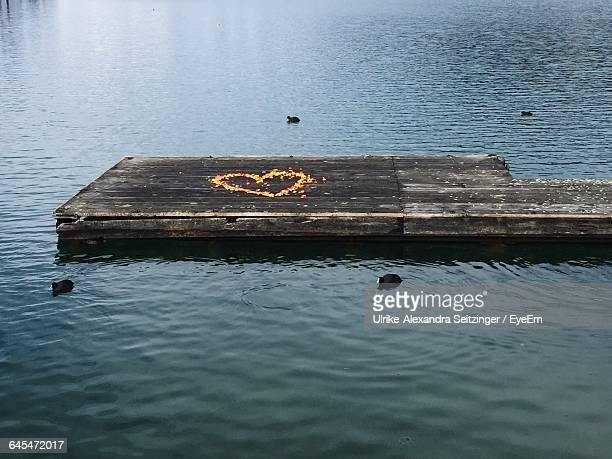 High Angle View Of Heart Shape Drawing On Pier In Lake