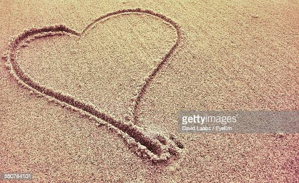 High Angle View Of Heart Shape Drawn In Sand On Beach