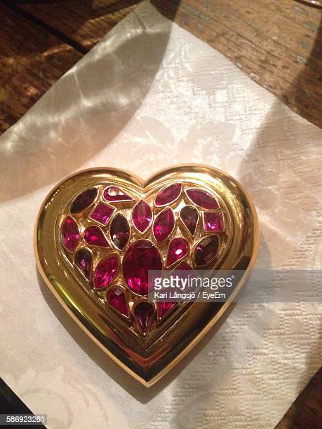 High Angle View Of Heart Shape Golden Pendent On Table