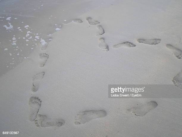 High Angle View Of Heart Shape Made Of Footprint At Beach