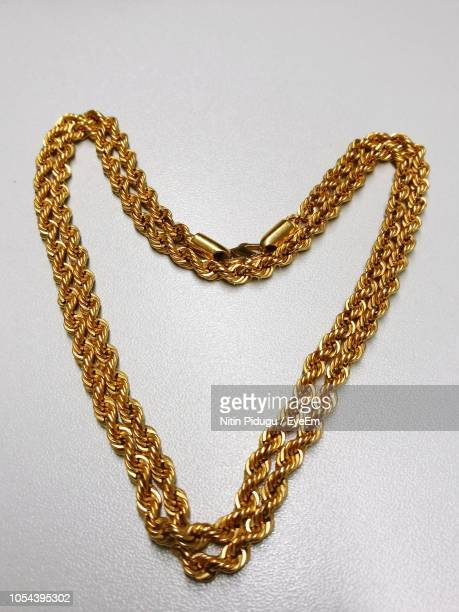 high angle view of heart shape made with chain over white background - halskette stock-fotos und bilder