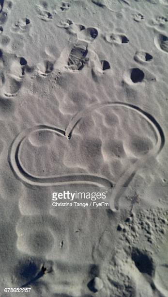 High Angle View Of Heart Shape On Sand During Sunny Day