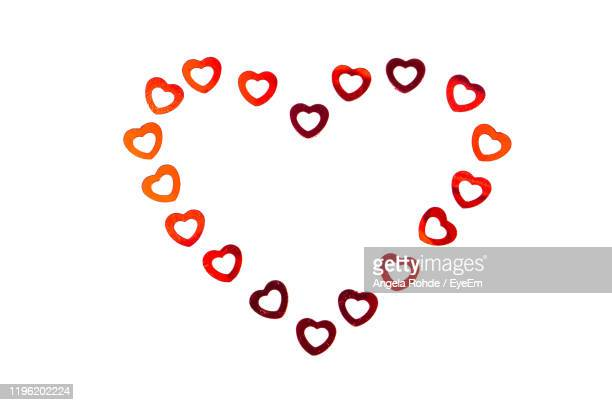 high angle view of heart shape over white background - angela rohde stock-fotos und bilder