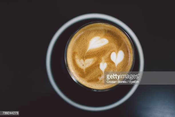 high angle view of heart shape pattern on coffee - bortes stock-fotos und bilder