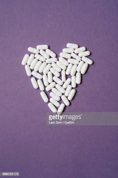 High Angle View Of Heart Shape Pills On Purple Background