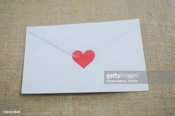 high angle view of heart shape stuck on white envelope on sack - love letter stock photos and pictures