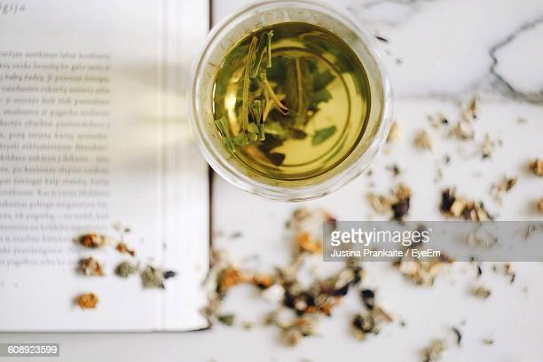 High Angle View Of Herbal Tea By Book On Table
