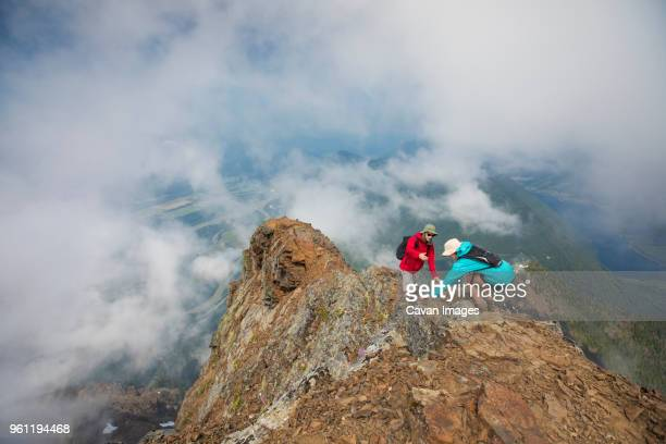 high angle view of hiker helping friend on mountain amidst clouds - doing a favor stock pictures, royalty-free photos & images