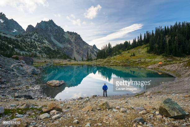 high angle view of hiker standing by lake against mountains at olympic national park - olympic park stock pictures, royalty-free photos & images
