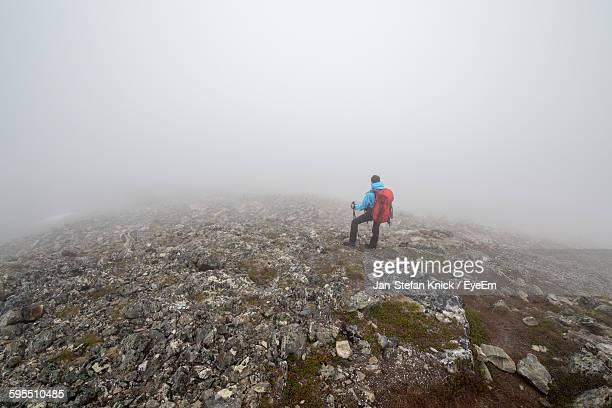 High Angle View Of Hiker Standing On Mountain Against Foggy Weather