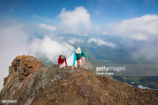 High angle view of hikers climbing mountain against cloudy sky