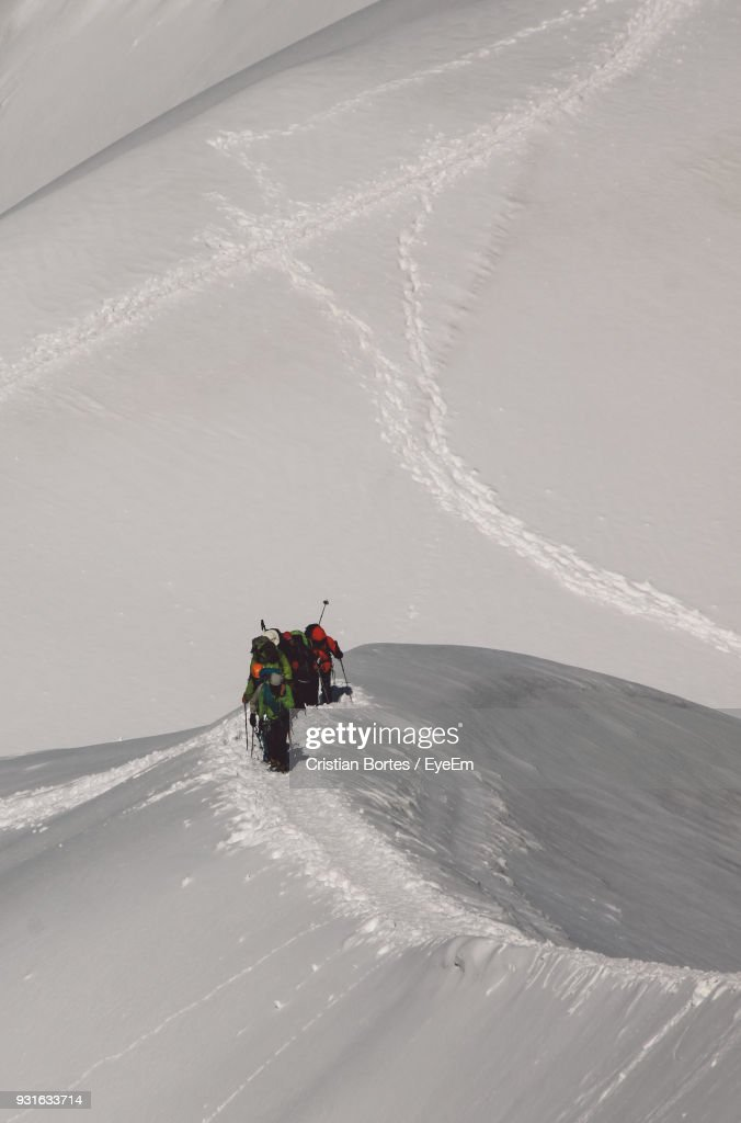 High Angle View Of Hikers Climbing Snowcapped Mountain : Stock Photo