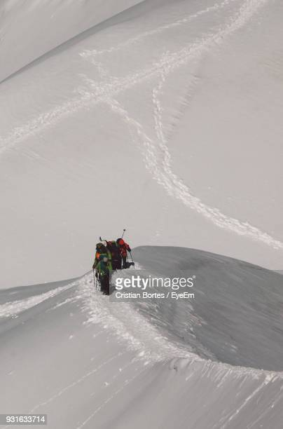 High Angle View Of Hikers Climbing Snowcapped Mountain