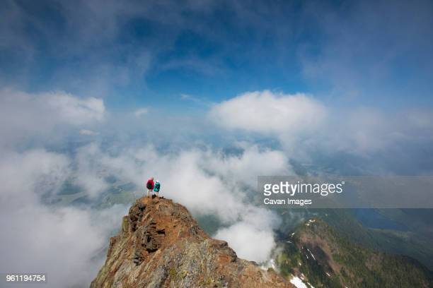 High angle view of hikers standing on Cheam Peak against sky amidst clouds