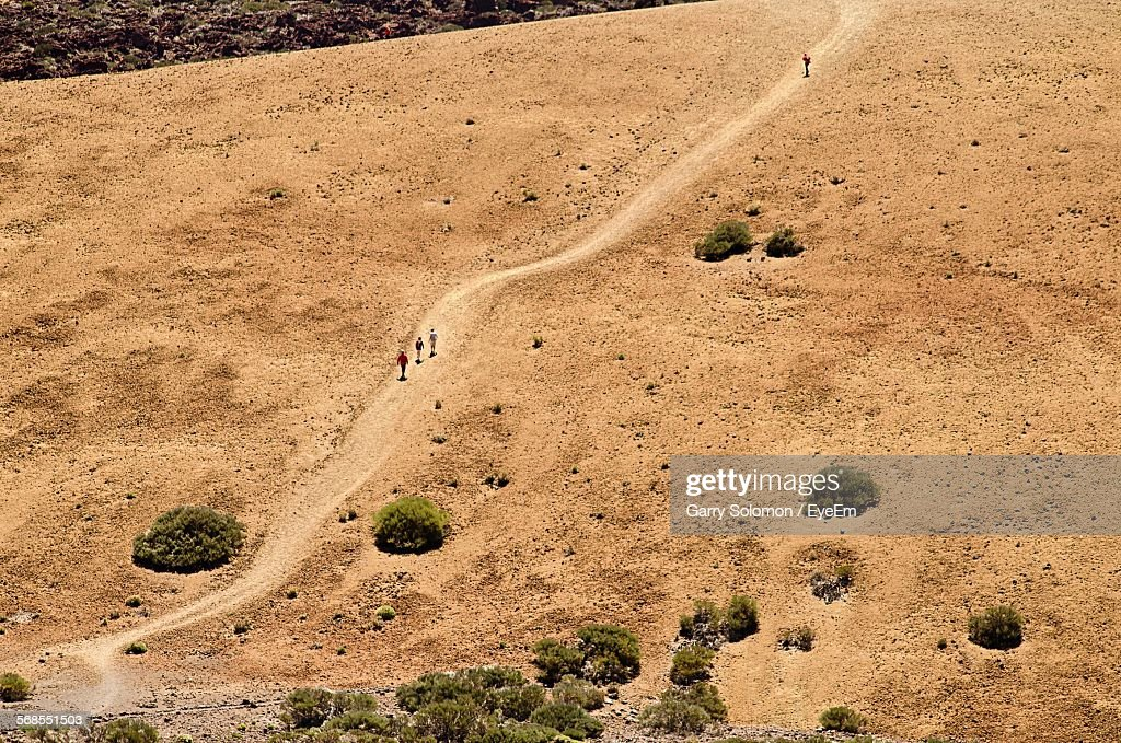 High Angle View Of Hikers Walking On Dirt Road : Stock Photo