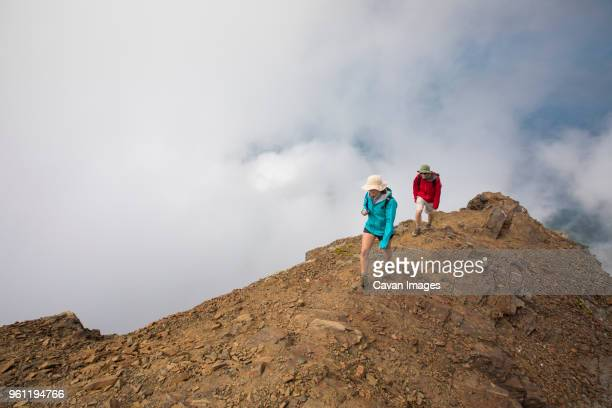 High angle view of hikers walking on mountain against cloudy sky