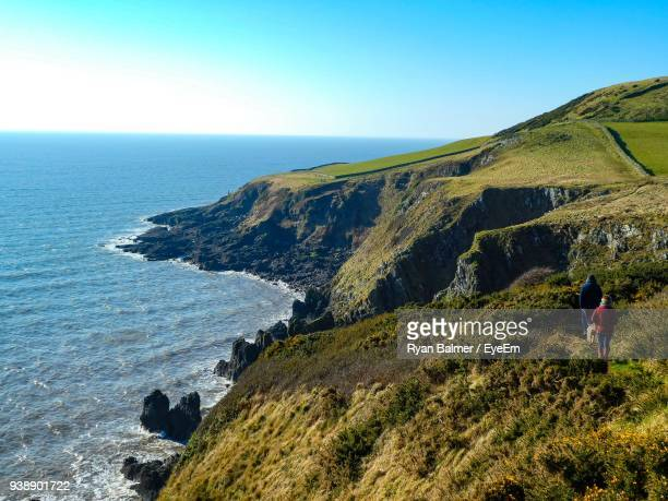 high angle view of hikers walking on mountain by sea against sky - dumfries and galloway stock pictures, royalty-free photos & images