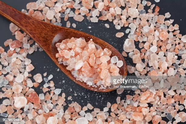 high angle view of himalayan salt with wooden spoon on table - himalayan salt stock pictures, royalty-free photos & images