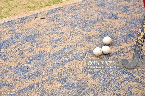 High Angle View Of Hockey Stick And Balls On Field