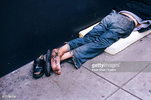 High Angle View Of Homeless Man Sleeping On Footpath